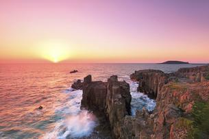北陸 東尋坊に寄せる波と夕日の写真素材 [FYI04630371]