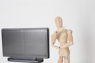 テレビを見て疑問を感じる人形の写真素材 [FYI04630651]