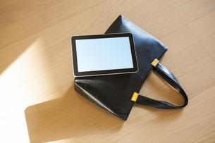 カバンの上に置かれたタブレットPCの写真素材 [FYI04631520]