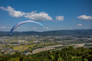 和歌山県紀の川市、寺山スカイスポーツからタンデム飛行に飛び立つパラグライダーの写真素材 [FYI04631716]