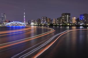 スカイツリーと永代橋 隅田川の屋形船の光跡の夜景の写真素材 [FYI04631745]