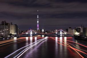 スカイツリーと清州橋 隅田川の屋形船の光跡の夜景の写真素材 [FYI04631748]