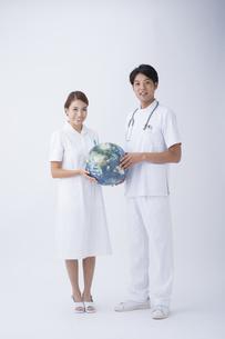 地球儀を持つ医者と看護師の写真素材 [FYI04632126]