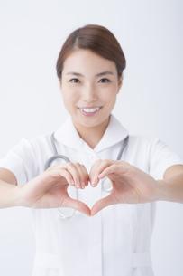 手でハートマークを作る看護師の写真素材 [FYI04632154]