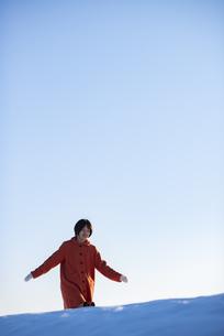 雪原を歩く若い女性の写真素材 [FYI04632241]