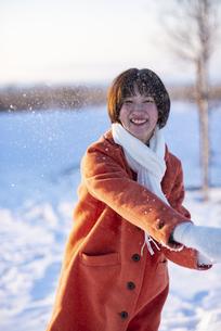 雪玉を投げる若い女性の写真素材 [FYI04632268]