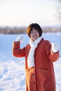雪玉を投げる若い女性の写真素材 [FYI04632269]