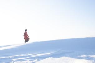 雪の上を歩く若い女性の写真素材 [FYI04632315]