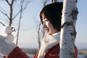 木立の中で雪だるまを見つめる若い女性の写真素材 [FYI04632325]