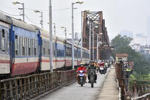 ロンビエン鉄橋を通過する列車とオートバイの写真素材 [FYI04633869]