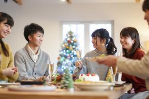 クリスマスパーティーで話をする若者の写真素材 [FYI04633972]
