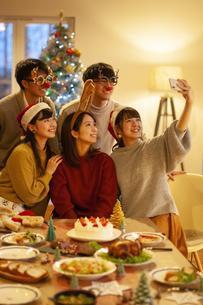 クリスマスパーティーで写真を撮る若者の写真素材 [FYI04633979]