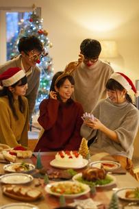 クリスマスパーティーでスマホを見る若者の写真素材 [FYI04633980]