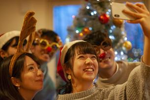 クリスマスパーティーで写真を撮る若者の写真素材 [FYI04633982]