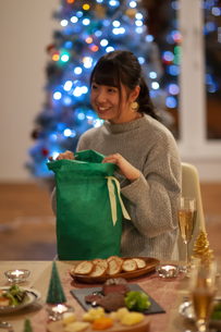 クリスマスプレゼントを開ける女性の写真素材 [FYI04633988]