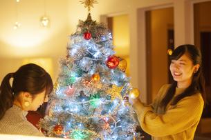 クリスマスツリーの飾り付けをする若者の写真素材 [FYI04634001]