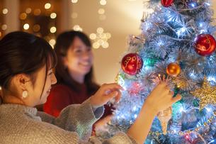 クリスマスツリーの飾り付けをする若者の写真素材 [FYI04634005]