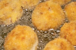 【料理】たくさんのコロッケを揚げる様子の写真素材 [FYI04634537]