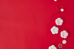 赤の背景と紅白の和菓子と梅の飾りの写真素材 [FYI04635194]