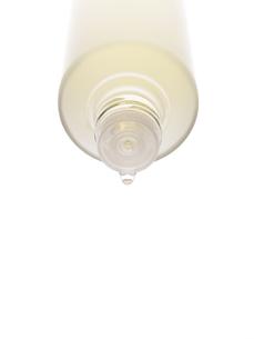 クリアなボトルから化粧水が滴れる瞬間の写真素材 [FYI04635439]