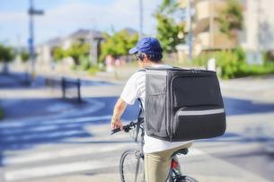 自転車でフードデリバリーをする配達員の後ろ姿の写真素材 [FYI04635677]