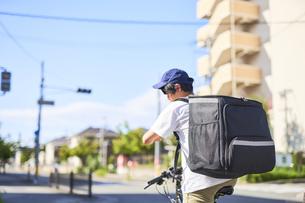 自転車でフードデリバリーをする配達員の後ろ姿の写真素材 [FYI04635679]