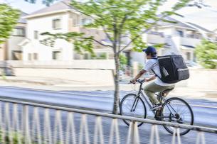 自転車でフードデリバリーをする配達員の写真素材 [FYI04635687]