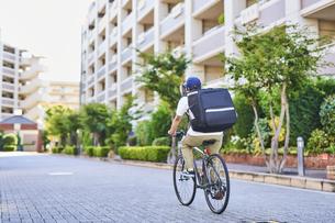 自転車でフードデリバリーをする配達員の後ろ姿の写真素材 [FYI04635690]