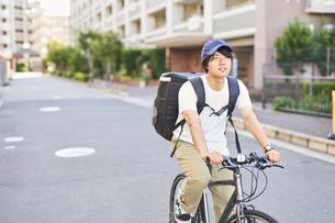 自転車でフードデリバリーをする配達員の写真素材 [FYI04635695]