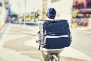自転車でフードデリバリーをする配達員の後ろ姿の写真素材 [FYI04635696]