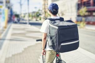 自転車でフードデリバリーをする配達員の後ろ姿の写真素材 [FYI04635697]