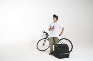 自転車を止めて立つフードデリバリーの配達員と白い背景の写真素材 [FYI04635699]