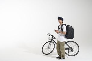 自転車を止めて立つフードデリバリーの配達員と白い背景の写真素材 [FYI04635700]