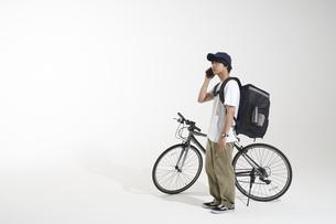 自転車を止めて電話をするフードデリバリーの配達員と白い背景の写真素材 [FYI04635701]
