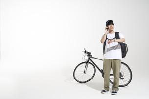自転車を止めて電話をするフードデリバリーの配達員と白い背景の写真素材 [FYI04635704]