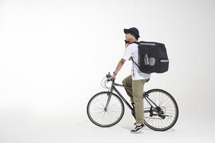 自転車に乗って電話をするフードデリバリーの配達員と白い背景の写真素材 [FYI04635707]