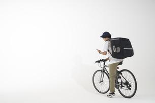 自転車に乗ったフードデリバリーの配達員と白い背景の写真素材 [FYI04635708]