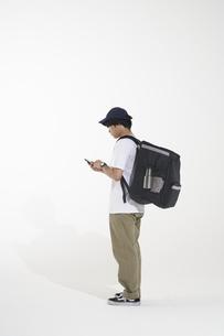 携帯電話を持ったフードデリバリーの配達員の写真素材 [FYI04635710]