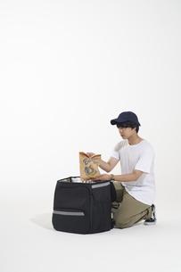 デリバリーのリュックから袋を出す配達員の写真素材 [FYI04635711]