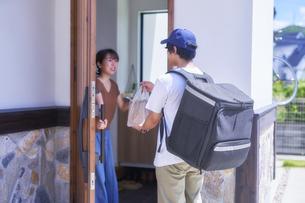 玄関で話すフードデリバリーの配達員と女性の写真素材 [FYI04635721]