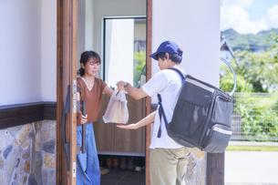 フードデリバリーの配達員から商品を受け取る女性の写真素材 [FYI04635725]