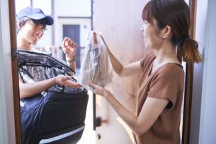 フードデリバリーの配達員から商品を受け取る女性の写真素材 [FYI04635733]