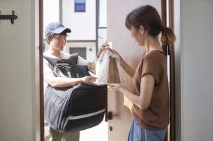 フードデリバリーの配達員から商品を受け取る女性の写真素材 [FYI04635736]