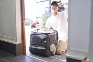 玄関でリュックから商品を出すフードデリバリーの配達員の写真素材 [FYI04635738]