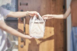 フードデリバリーの配達員から商品を受け取る女性の手元の写真素材 [FYI04635740]