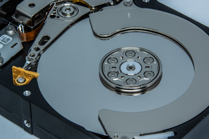 ハードディスクドライブ(HDD)の蓋を開けた中の様子。白い背景。の写真素材 [FYI04636049]