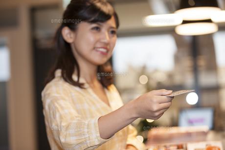 カードを持つ笑顔の女性の写真素材 [FYI04636319]