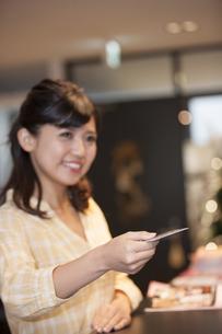 カードを持つ笑顔の女性の写真素材 [FYI04636321]