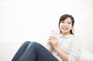 スマホを持つ笑顔の女性の写真素材 [FYI04636361]