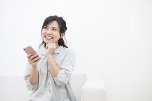 スマホを持つ笑顔の女性の写真素材 [FYI04636362]